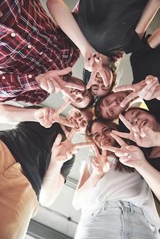 Felice gruppo di amici con le mani insieme al centro.