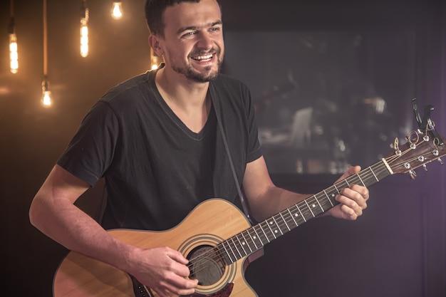 Il chitarrista felice in una maglietta nera suona una chitarra acustica in un concerto su uno sfondo nero sfocato.