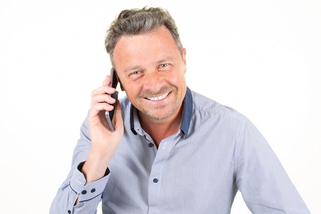 Uomo casuale del tipo felice che sta chiacchierante sul cellulare dello smartphone nel fondo bianco