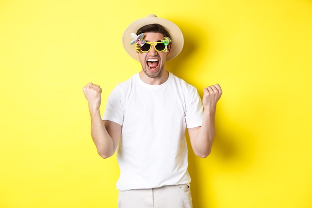 Ragazzo felice che va in vacanza, vince o festeggia, indossa cappello estivo e occhiali da sole. turista che sembra eccitato, in piedi su sfondo giallo.