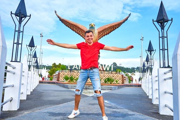 Turista felice del tipo che posa accanto alla scultura di un'aquila rossa che spande le sue ali. località turistica popolare sull'isola di langkawi