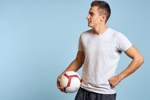 Ragazzo felice con pallone da calcio in mano su sfondo blu gioca a calcio e vista ritagliata