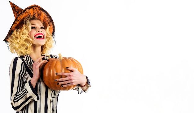 Felice halloween. ragazza emotiva con cappello da strega con jack-o-lantern. donna sorridente con zucca. cibo tradizionale. copia spazio.