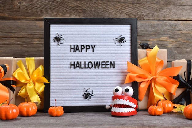 Felice halloween. composizione festiva per halloween su fondo in legno con zucche e regali. copia spazio.