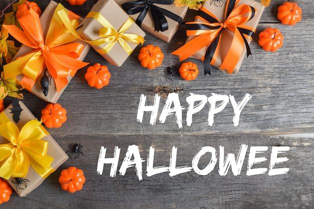 Felice halloween. composizione festiva per halloween su fondo in legno con zucche e regali. vista dall'alto. Foto Premium