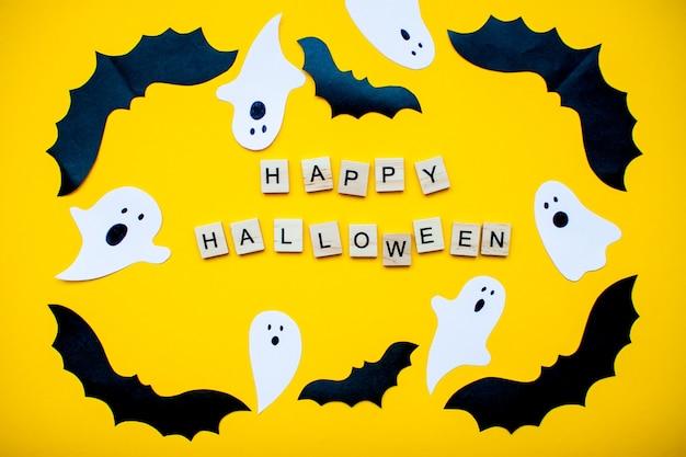Happy halloween e cornice fatta di pipistrelli di carta fatti in casa e fantasmi di carta su uno sfondo giallo brillante
