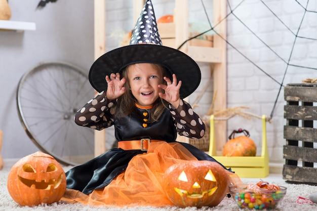Felice halloween. una bella ragazza in costume da strega celebra una casa in un interno con zucche