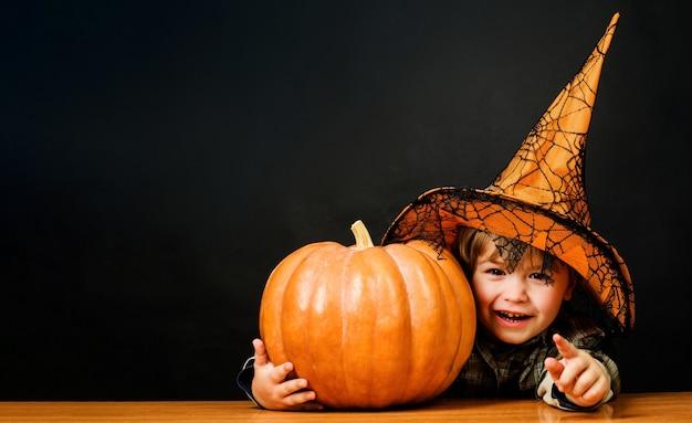 Felice halloween. ragazzino con cappello da strega con zucca di halloween che punta a te. dolcetto o scherzetto. bambino con jack-o-lantern.