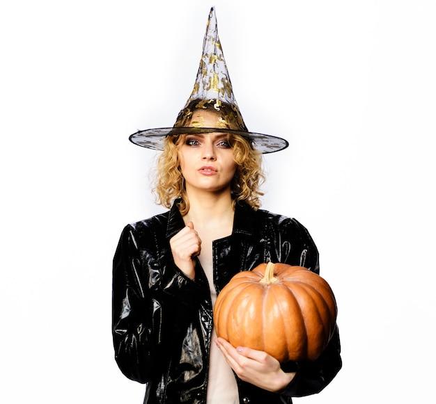 Felice halloween. strega sexy della ragazza con la zucca. cibo tradizionale. donna seria in cappello e costume delle streghe con zucca arancione.