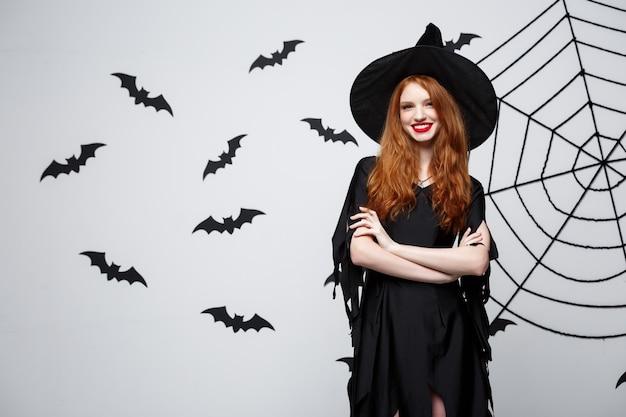 Tenuta felice della strega di halloween che posa sopra il fondo grigio scuro dello studio con il pipistrello e la ragnatela.