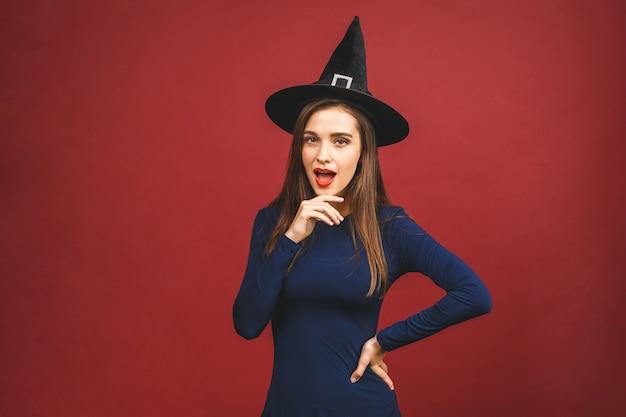 Happy halloween strega con trucco luminoso e capelli lunghi. bella giovane donna sorpresa che posa in costume sexy delle streghe. isolato su sfondo rosso