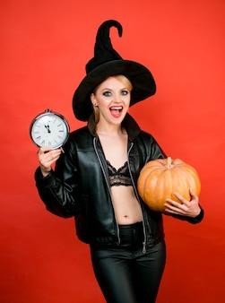 Felice halloween giovani donne in nero strega costumi di halloween sulla festa su sfondo rosso faccine divertenti...