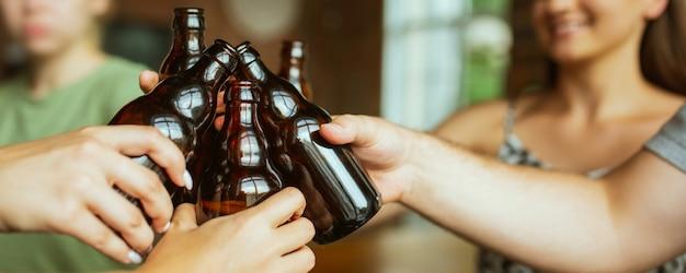 Felice. mani di amici, colleghi mentre bevono birra, si divertono, tintinnano bottiglie, bicchieri insieme.