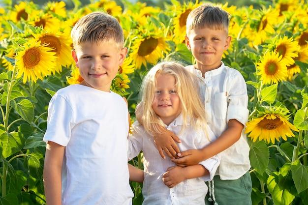Bei ragazzi felici stanno in un campo di girasoli in fiore