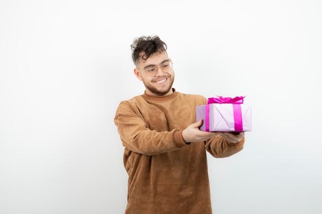 Uomo bello felice che tiene il suo regalo di festa sopra bianco.