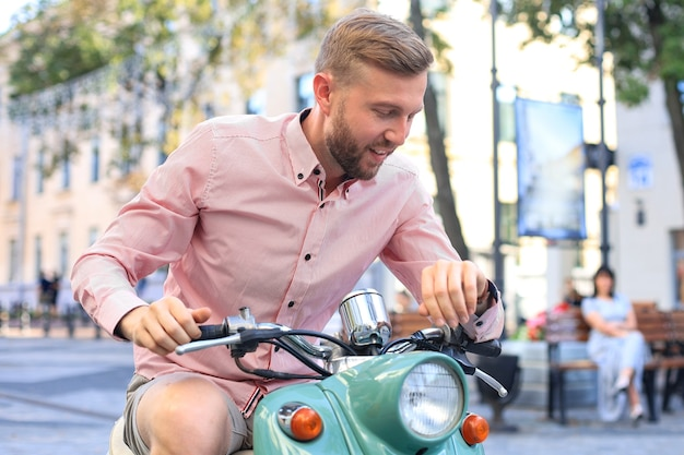 Felice bell'uomo in sella a uno scooter in città.