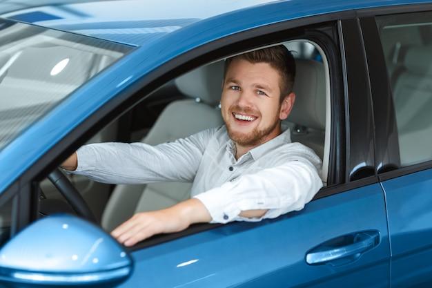 Uomo bello felice che sorride allegramente alla macchina fotografica mentre era seduto nella sua nuova auto presso la concessionaria