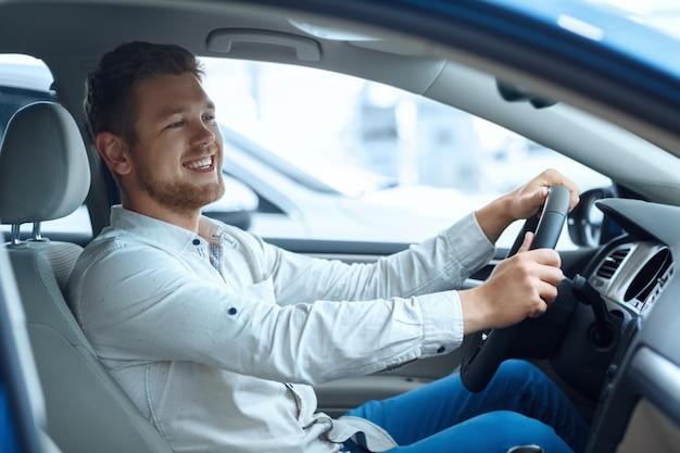 Uomo bello felice che sorride con gioia mentre provando una nuova auto presso la concessionaria