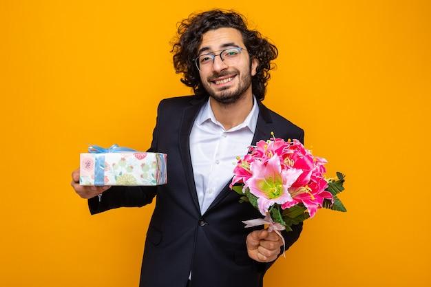 Felice bell'uomo in abito che tiene presente e bouquet di fiori guardando la telecamera sorridendo allegramente celebrando la giornata internazionale della donna 8 marzo in piedi su sfondo arancione