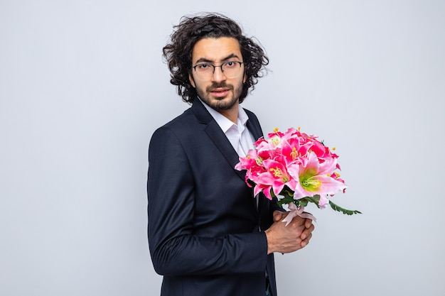 Felice bell'uomo in abito con bouquet di fiori che guarda l'obbiettivo sorridente fiducioso che celebra la giornata internazionale della donna l'8 marzo in piedi su sfondo bianco