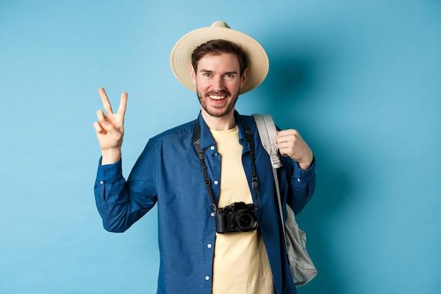 Uomo bello felice che cattura foto durante le vacanze estive, mostrando il segno di pace e sorridente, indossando cappello di paglia e tenendo lo zaino turistico, sfondo blu.
