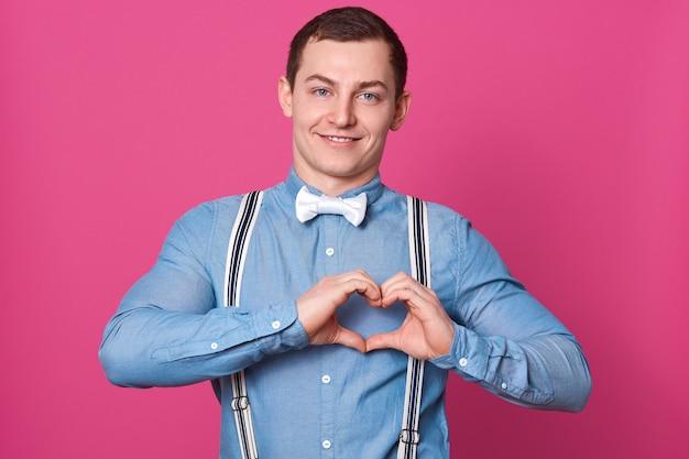 Uomo bello felice che indossa camicia blu e farfallino bianco che sta con il gesto di amore o del cuore e che guarda direttamente con il sorriso piacevole. colpo dell'interno, isolato sopra la parete rosa