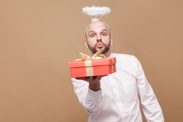 Felice bello angelo barbuto calvo di mezza età in camicia e aureola bianca sulla testa in piedi con un regalo rosso, guardando la macchina fotografica e mandando un bacio. girato in studio al coperto, isolato su sfondo marrone chiaro.