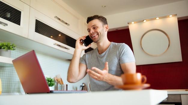 Felice bell'uomo moderno che parla al telefono mentre lavora al laptop in cucina