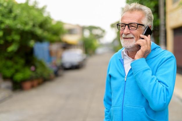 Uomo barbuto anziano bello felice che sorride mentre parla sul telefono cellulare e pensa con gli occhiali all'aperto