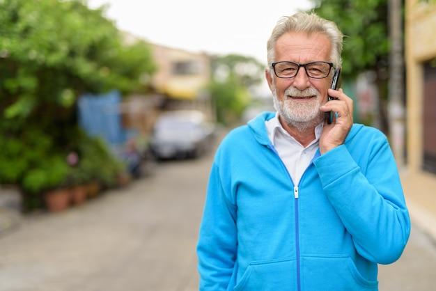 Uomo barbuto anziano bello felice che sorride mentre parla sul telefono cellulare e indossa occhiali all'aperto
