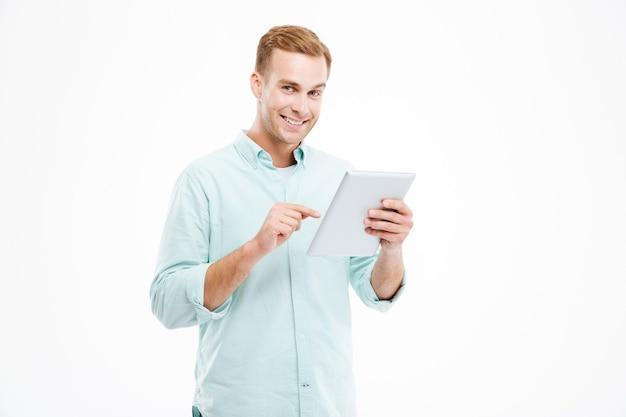 Felice bel ragazzo sorridente che utilizza tablet isolato su un muro bianco