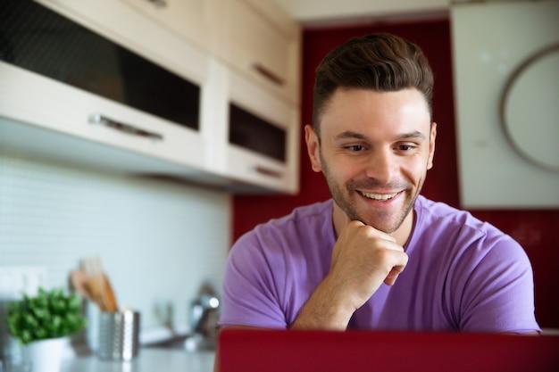 Felice bel giovane sorridente in abiti casual è seduto mentre lavora al suo computer portatile nella moderna cucina di casa