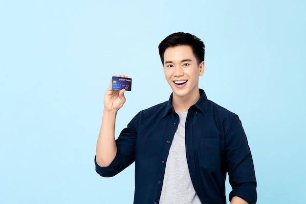 Giovane uomo asiatico bello felice che mostra la carta di credito isolata