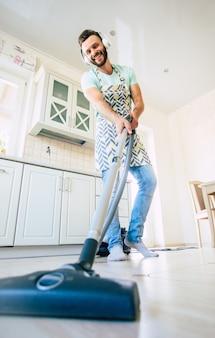 Felice bel giovane barba uomo sta pulendo il pavimento nella cucina domestica e divertirsi.