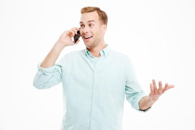 Felice bel giovane uomo d'affari che parla al telefono cellulare su un muro bianco