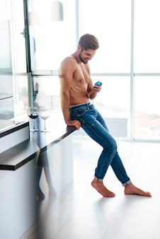 Felice bel giovane in jeans che usa il telefono cellulare in cucina