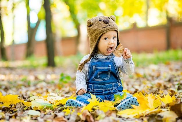 Felice, felice baby sitter nel parco con foglie gialle in autunno in berretto da orso.