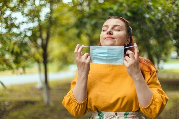 Felice ragazza felice si toglie la maschera medica protettiva dal viso per respirare aria fresca