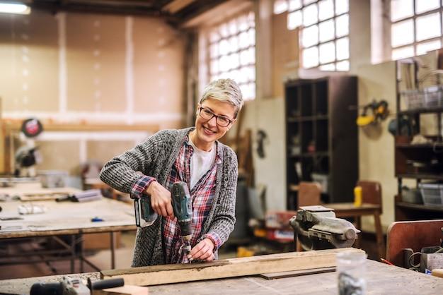 Felice lavoratrice felice lavorando con trapano elettrico nella sua officina