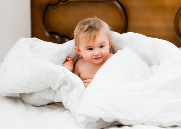 Bambino felice e sano di 11 mesi seduto sul letto sotto una coperta bianca e ridendo. concetto di bambino