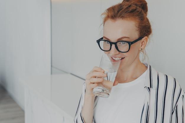 Felice bella giovane donna rossa in buona salute che beve acqua al mattino a casa