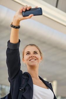Felice ragazza in buona salute che lavora e si allena tenendo i selfie