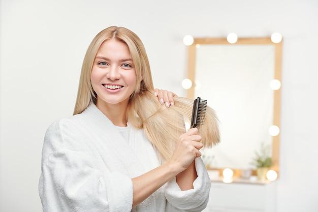 Giovane donna felice e in buona salute con il sorriso a trentadue denti che spazzola i suoi capelli biondi lunghi