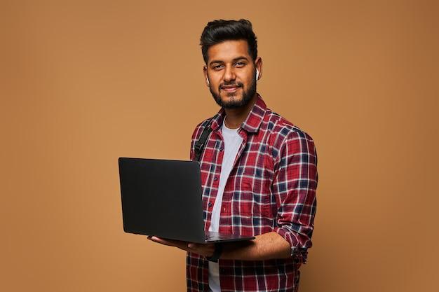 Felice manager indù in chiusura casual con laptop su muro pastello