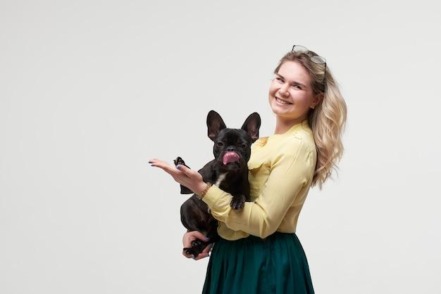 Donna felice dei pantaloni a vita bassa che gioca con il bulldog francese sulla parete bianca
