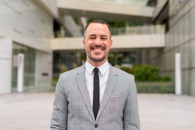 Uomo d'affari barbuto calvo ispanico felice che sorride nella città all'aperto