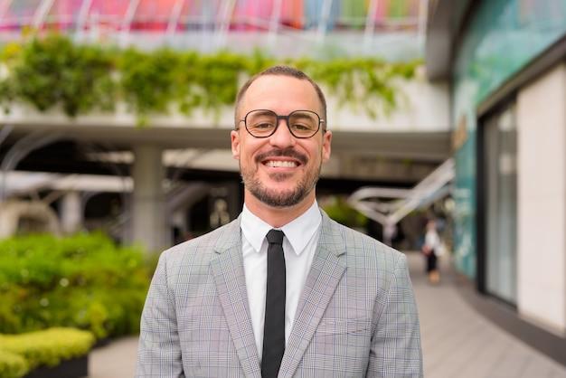 Uomo d'affari barbuto calvo ispanico felice con gli occhiali sorridente fuori dall'edificio moderno