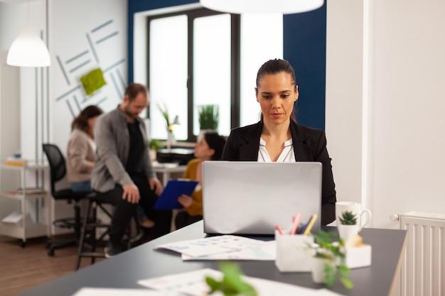 Felice signora ispanica che digita sul computer portatile seduto alla scrivania nell'ufficio di avvio aziendale che beve caffè mentre diversi colleghi lavorano in background