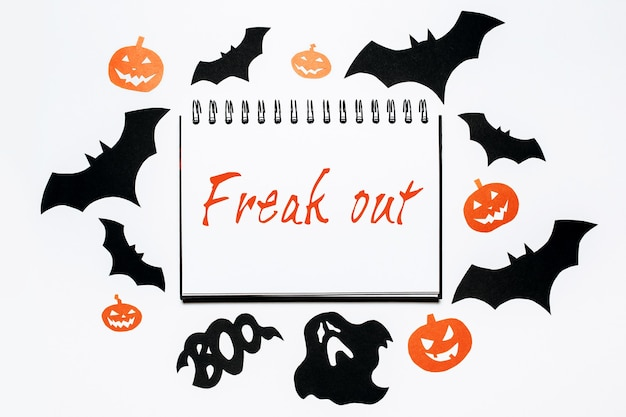 Felice concetto di vacanza. blocco note con il testo di halloween freak out sulla superficie bianca