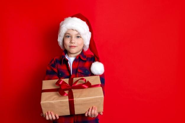 Buone vacanze e buon natale. ritratto di un ragazzo con un berretto con doni in mano su uno sfondo rosso. un posto per il testo. foto di alta qualità